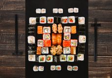 Set of sushi, maki and rolls on brown wood background Royalty Free Stock Photos