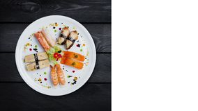 Japanese food. Rotating sashimi set on a white round plate, decorated with small flowers, top view. Black wooden stock video