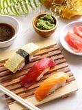Japanese food salmon nigiri, tuna nigiri, and tamago nigiri sush. Portrait of salmon nigiri, tuna nigiri, and tamago nigiri sushi served on wooden plate with Royalty Free Stock Photos