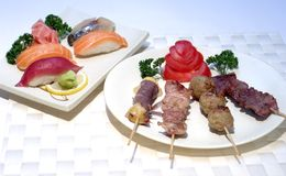 Japanese Food, Skewers, and Su. Japanese Food, Plate of Cooked Barbecued Meats and Cheese sticks; skewers, and Salmon Sushi Yakitori Royalty Free Stock Image