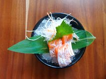 Japanese food style, Top view of salmon belly sashimi with bamboo leaves on ice. In black bowl on wooden table in Restaurant, salmon toro sashimi is japanese royalty free stock images
