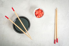 Japanese food, sushi. Concept of Japanese food: sticks for sushi, soy sauce and pickled ginger on a white stone table. Top view copy space Stock Photos