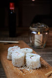 Japanese food, sushi roll with crab, sesame seeds, cucumber, cheese, on a wooden board Royalty Free Stock Images