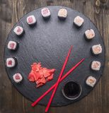 Japanese food, sushi with salmon and tuna, fresh ginger, soy sauce and chopsticks lined up on  tray of chalk boards, frame, space Stock Photo