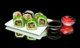 Japanese food - sushi, soy sauce and pickled ginger on a black b Royalty Free Stock Photography