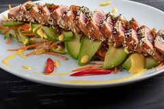 Free Japanese Food. Tataki With Tuna. Fried Fish With Sesame Seeds And Soy Sauce, Wasabi, Lime. On A Pillow Of Vegetables. Avocados, Stock Photo - 170929440