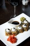Japanese food on a white plate with glasses of wine royalty free stock photography