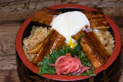 Japanese fusion dish with spicy rice with tamari sauce, roasted eel, egg and red turnip. In a decorated bowl, dark wood table background stock photo