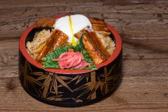 Japanese fusion dish with spicy rice with tamari sauce, roasted eel, egg and red turnip. In a decorated bowl, dark wood table background royalty free stock images