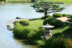 Japanese Garden. A Japanese lantern sits prominently by the water Royalty Free Stock Image