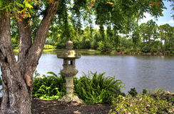 Japanese Garden. Japanese statuary in the shade of a tree by the lake Stock Photography