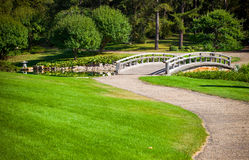 Japanese garden. Bridge over the pond and green grass around Royalty Free Stock Photography