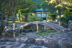 Japanese garden bridge over a stream royalty free stock photo