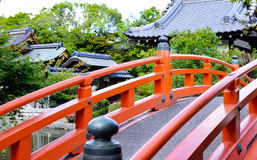 Japanese garden bridge. A vermilion arched footbridge going over a pond with Shinsen`en Shrine in the background, Kyoto, Japan Stock Photo