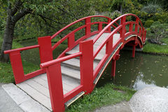 Japanese garden bridge. Vivid red over the water Stock Image