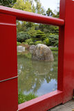 Japanese garden bridge. Vivid red over the water Royalty Free Stock Photography