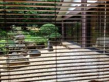 Japanese garden in courtyard. Courtyard garden view through shutters stock photography