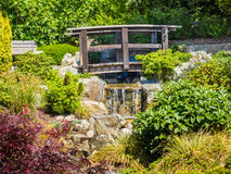 Japanese garden design with waterfall and bridge Royalty Free Stock Photo