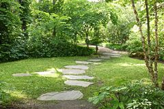 Japanese garden flagstone walk. The beautiful flagstone walkway leads you through an open area in a peaceful japanese garden Royalty Free Stock Photography