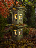 Japanese garden lamp with autumnal leaves Royalty Free Stock Photos