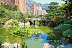 Japanese garden of Monaco. With a Japanese house and a pond and Monte Carlo buildings behind Stock Photos