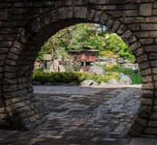 Japanese Garden through Moon Gate. View of Japanese garden, lake and red pagoda through stone brick moon gate stock images