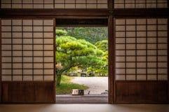 Japanese garden seen through sliding door. Royalty Free Stock Photography