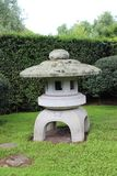 Japanese Garden statue. Concrete white statue in Japanese Garden on bright day with green background Royalty Free Stock Photo
