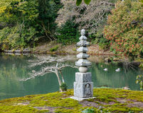 Japanese garden with the stone tower at the Kinkaku temple in Kyoto, Japan Stock Photos