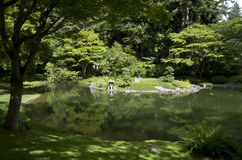 Japanese garden. Typical Japanese garden with beautiful pond, island, rock bank, lantern and reflections. Nitobe Memorial Garden, Vancouver, Canada Royalty Free Stock Images