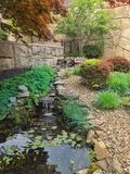 Japanese garden with water feature. Fountain Cascades down rocks in this shade reflection pond Stock Photography