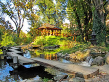 Japanese garden with a water pool, pavilion and wooden bridge Stock Image