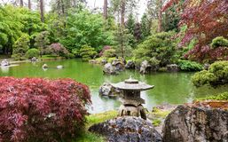 Japanese garden with pond, lantern, trees and beauty. Japanese gardens provide a sense of peace and harmony. On this rainy afternoon all elements are at work royalty free stock photography