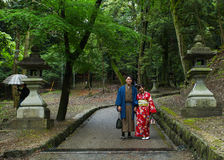 Japanese Geisha and partner. At Fushimi Inari Shrine gardens  in Kyoto Stock Photo