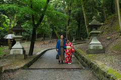 Japanese Geisha and partner at Fushimi Inari Shrine gardens  in Kyoto. The road to the top of the mountain is reachable by a path lined with thousands of torii Royalty Free Stock Image