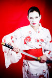Japanese Geisha with sword. A young woman dressed as a Japanese Geisha with a sword Stock Photo