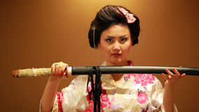 Japanese geisha with sword. Japanese geisha samurai with sword on orange background Royalty Free Stock Photography