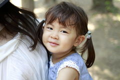 Japanese girl carried in her mother`s back. 2 years old Royalty Free Stock Images