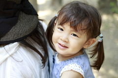 Japanese girl carried in her mother`s back. 2 years old Royalty Free Stock Photo