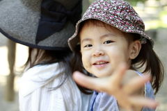 Japanese girl carried in her mother`s back. 2 years old Stock Photos