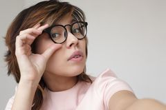 Japanese girl corrects glasses. She looks into the camera doubtfully royalty free stock image