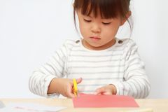 Japanese girl cutting paper with scissors. 3 years old royalty free stock images