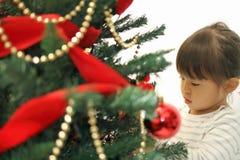 Japanese girl decorating Christmas tree Royalty Free Stock Photography