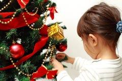 Japanese girl decorating Christmas tree Royalty Free Stock Images