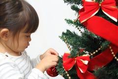 Japanese girl decorating Christmas tree Royalty Free Stock Photo