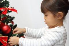 Japanese girl decorating Christmas tree Stock Image