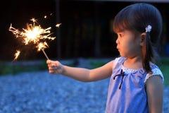 Japanese girl doing handheld fireworks. 2 years old Royalty Free Stock Image