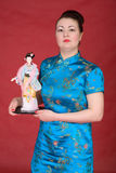 Japanese girl with doll. On the red background Royalty Free Stock Photography