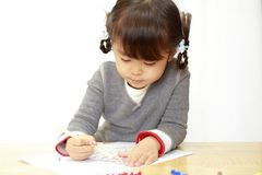 Japanese girl drawing a coloring book. 4 years old royalty free stock image