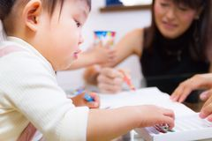 1-year-old girl immersed in drawing pictures with friends. Japanese girl drawing pictures with her friends Stock Photography